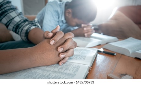 Two christian praying on wooden table with bible.