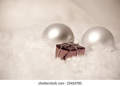 Two Christmas balls and red package in the front with antique colors.
