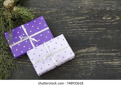 Two Christmas gifts on a dark wooden surface
