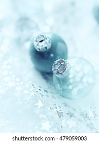 Two Christmas ornaments on a white organza