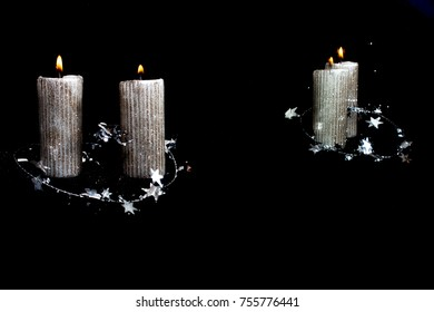 Two Christmas silver candles on the black background with stars and reflection in mirror, free space for text.