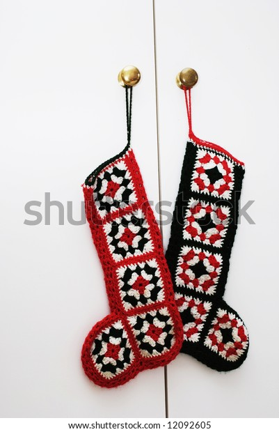 Two Christmas stockings hanging on a cupboard door.