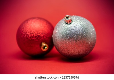 Two Christmas tree decoration balls isolated on a red background