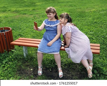 Two chubby happy little girls with interest communicate with someone on a smartphone. They are sitting on a park bench on the lawn in the summer on a sunny day
