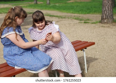Two chubby young girls met in a park on a bench. They are watching with interest something on the smartphone. Around deserted after quarantine