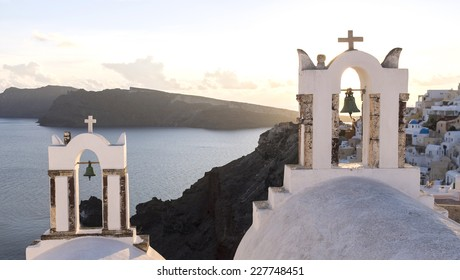 Two church structures during sunset in the village of Oia on the popular Greek Island of Santorini in the Mediterranean. Santorini is located in the Aegean Sea and belongs to the Cyclades islands.