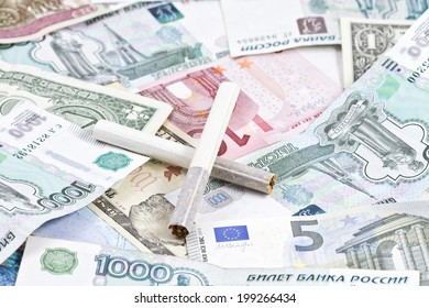 two cigarettes lying on the money
