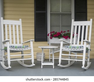 Two classic American rocking chairs on the front porch of a home.