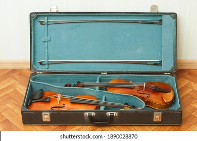 Two classical violins with bows in a double case
