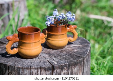two clay cups with tea and flowers on a wooden stump and green grass/ free space for text