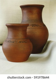 Two clay pots on the background of linen cloth with pleats close up