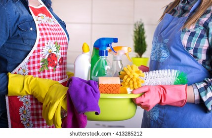 Two cleaning women holding basin full of cleaning supplies in the kitchen. House keeping and teamwork concept