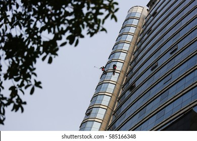 two cleaning workers (high altitude spider man) clean the glass walls on a tall office building. High altitude operation safety is very important.