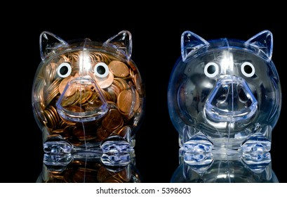 """Two clear acrylic piggy banks one stuffed full of american pennies the other empty, Illustration of the """"haves"""" and the """"have nots"""""""