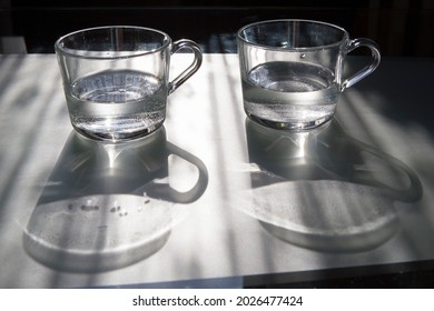 Two clear glass cups with water and their shadows on a table