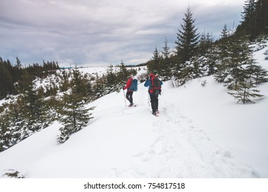 Two climbers are climbing mountains in winter, men with backpacks and Hiking sticks are on the snow on background of forest and sky with cloud.