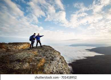 Two climbers standing on top of summit above clouds in the mountains. Hiker man pointing with his hand discussing route. Plan, vision and mission concept.