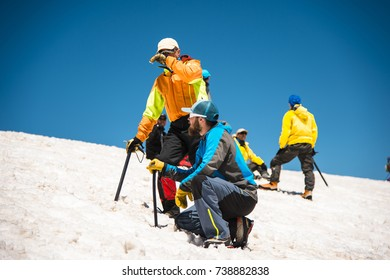 Two climbers talk on training on the right slip on the slope with an ice ax for non-stop braking