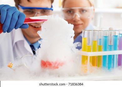 Two clinicians making experiment with steaming liquid in laboratory