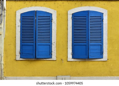 Two closed blue window shutters and a yellow wall in Verdun, France
