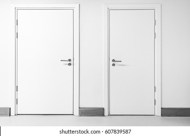 Two closed doors inside of the corridor.