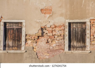 two closed windows with wooden shutters on wall of the old shabby house