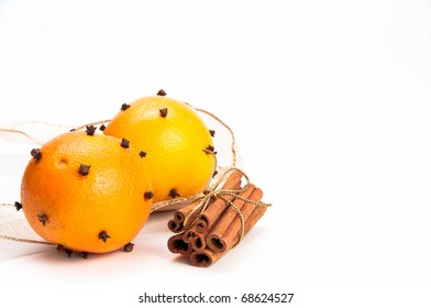 Two cloves-decorated oranges and cinnamon sticks in the stack with gold ribbon, gold ribbon in the background, white, isolating background
