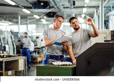 TWO CNC machine operators examining finished products and writing notes in industrial facility.