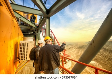 Two coal mine engineers with protective helmets standing and talking on a huge drill machine, talking and watching at the digging site. Beautiful and colorful sky in the background. Rear view.