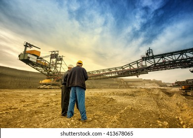Two coal mine engineers with protective helmets standing in front of huge drill machine, chatting and watching at the digging site. Beautiful and colorful sky in the background. Rear, wide angle view.