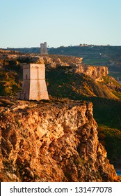 Two Coastal defense towers awash in the golden light of sunset, silent sentinels of the past, forming part of the defensive perimeter built by the Knights of St John during their 200 year stay
