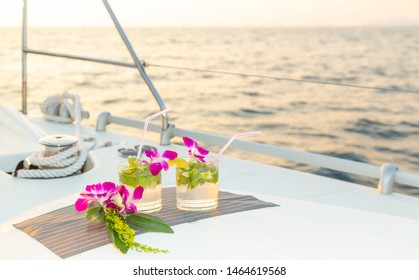 Two cocktail glasses with floral decorations and a straw on the deck of a luxury sailing yacht at sea during a cruise on the Andaman Sea of the Indian Ocean. Fresh alcohol mojito and gin cocktails.