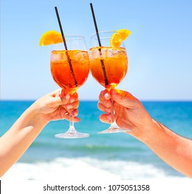 Two cocktail glasses in the hands on sea background. Summer vacation concept