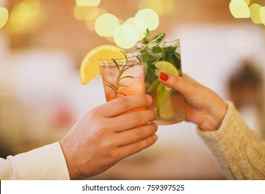 Two cocktail glasses in man and woman hand. Close up