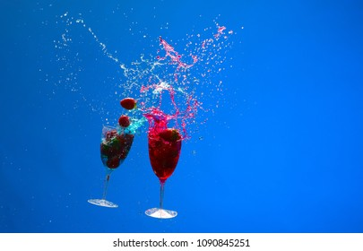 Two cocktail glasses with strawberries in a splash