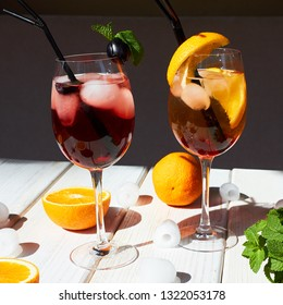 two cocktails aperol and kir royal on a white wooden table, a half an orange and ice, and mint are next to it. direct sunlight