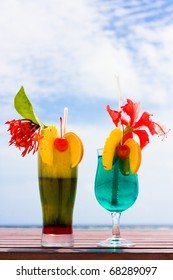 Two cocktails on a table at shore of ocean