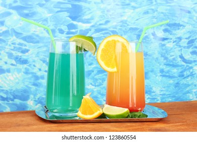 Two cocktails on tray on blue background