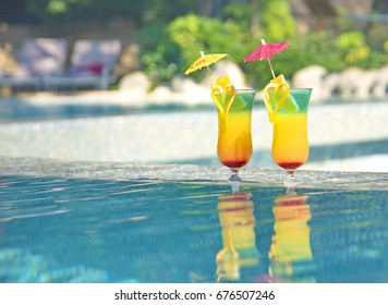 Two cocktails at pool background