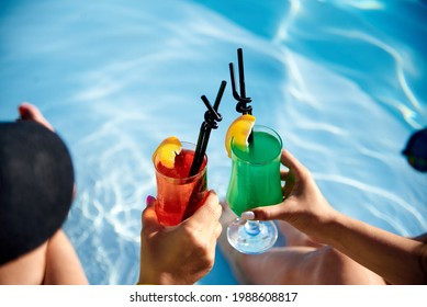 two cocktails in women's hands on the background of water - Shutterstock ID 1988608817
