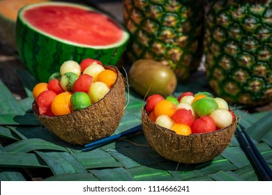 two coconut shells filled with a fruit salad with marbles of all colors