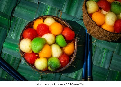 two coconut shells filled with a fruit salad with balls of all colors