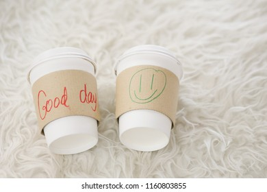 "Two coffee cups with the hand writing word  ""Good day"" and drawing smaile icon on hot cup sleeve with white rug."
