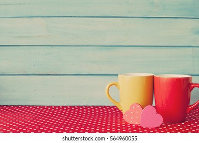 Two coffee cups and hearts over polka dots tablecloth and turquoise wood background