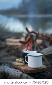 Two coffee cups and homemade cookies near campfire. Black and white. Warm and cold. Camping.