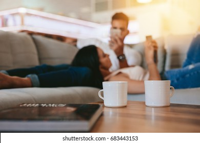Two coffee cups on table with couple relaxing in background on couch. Cups of coffee in front with man and woman at the back at home.