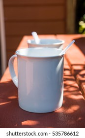 Two coffee cups under the sunlight.
