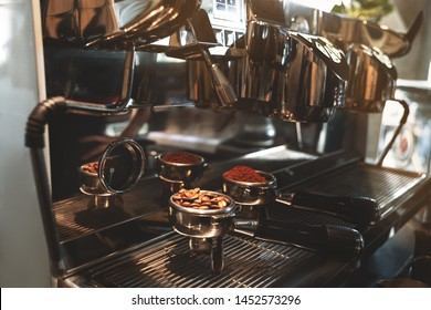 two coffee holders one with fresh ground coffee another with roasted beans standing on professional coffee machine close up