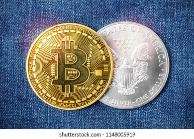 Two coins of gold bitcoin and a silver dollar on the background of jeans. Subject of Finance and Economy
