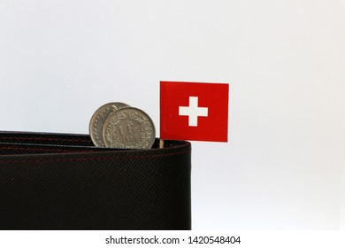 Two coins of one swiss Franc and mini Switzerland flag stick on the black wallet with white background. Franc Schweiz money, the concept of finance.